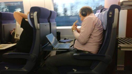 Mann schaut im ICE Film auf dem Tablet, während er isst und sein Arbeits-Notebook vor ihm steht