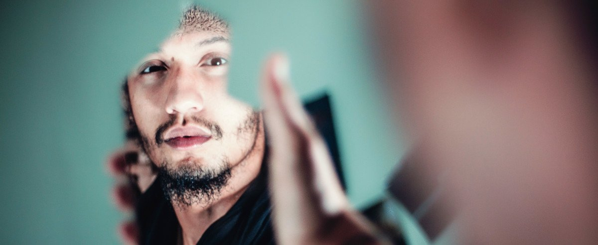 Mann schaut sich selbst im Spiegelglas an