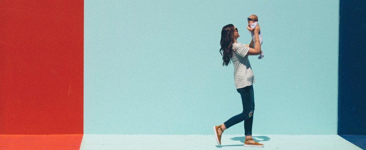 Mutter trägt Kind auf dem Arm vor einer bunten Wand