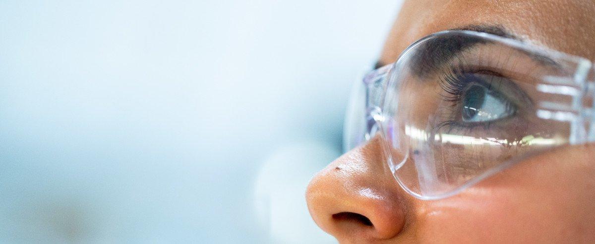 Eine junge Wissenschaftlerin mit Schutzbrille aufgesetzt