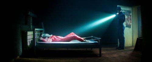 Szenenbild aus Film Kidnapping Stella: Stella liegt gefesselt im Bett, der Entführer strahlt sie mit einer Taschenlampe aus der Entfernung an