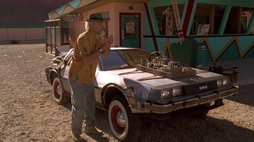 Doc Brown steht im Western fragend vor dem DeLorean