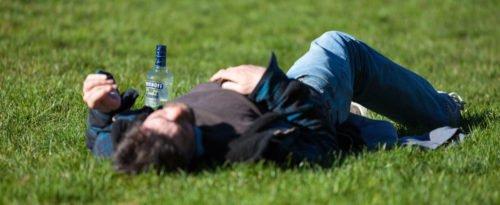 Ein Mann, der betrunken auf einer Wiese liegt, neben ihm eine Flasche Wodka.