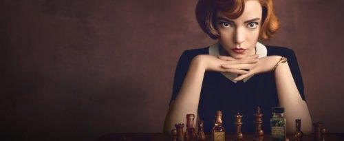 Die Protagonisten sitzt vor einem Schachbrett und blickt den Zuschauer direkt an