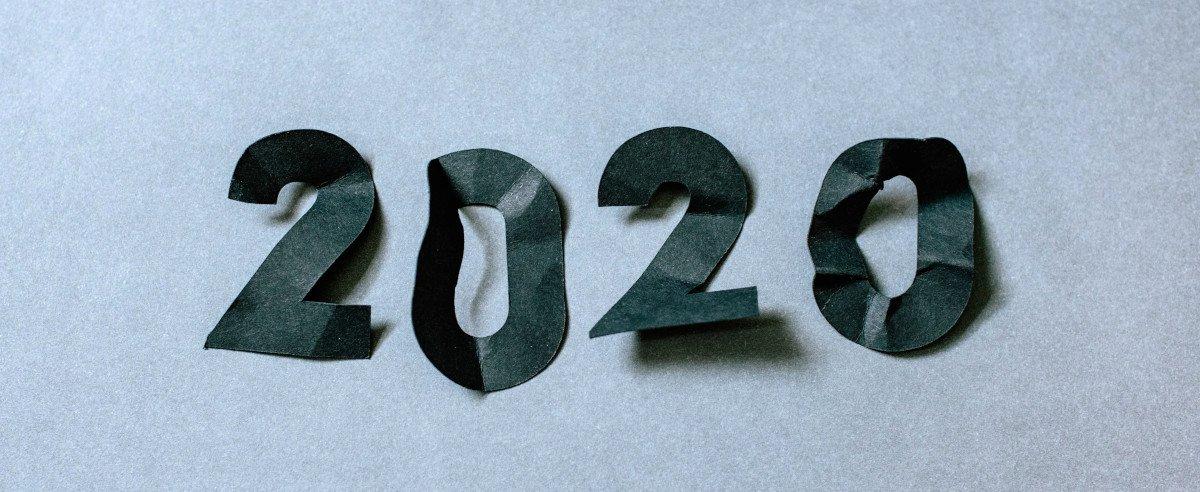 """Die Zahlen """"2020"""" in schwarzem, zerknitterten Papier auf weißem Untergrund"""
