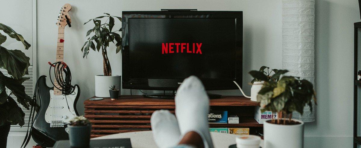 Ein Fernseher mit Netflix-Logo, davor zwei Füße auf einem Tisch beim entspannten Fernsehen