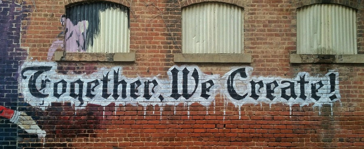 Grafitti auf Ziegelwand, Beschriftung: Together We Create