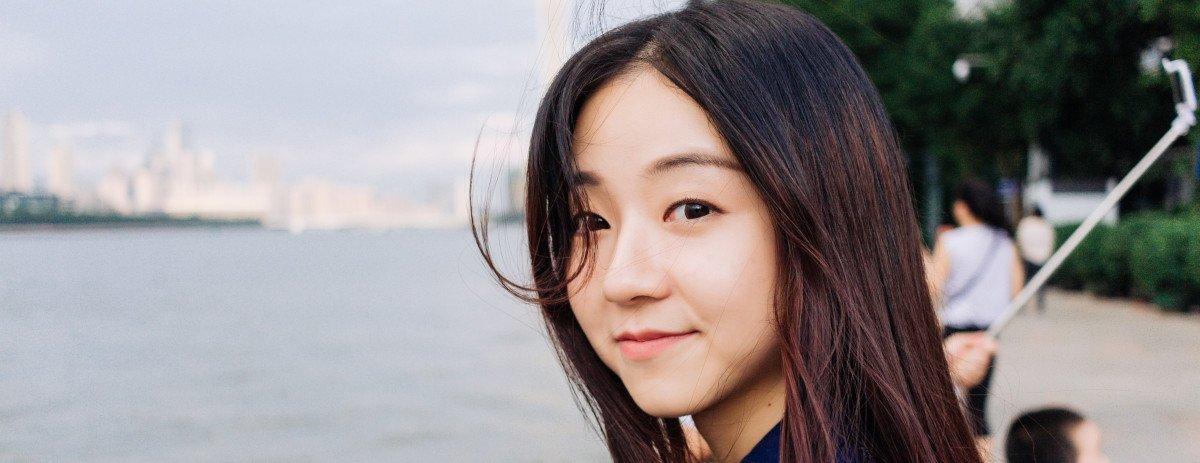 Eine Frau mit asiatischem Phänotyp befindet sich an einem Kanal und schaut direkt an die Kamera