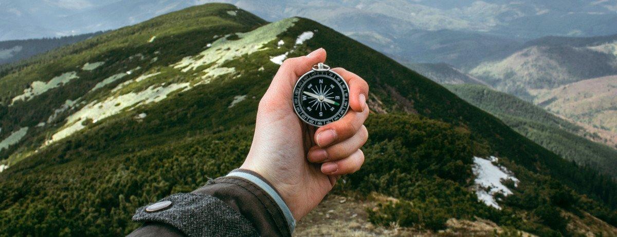 Eine Hand vor einem Bergpanorama. Die Hand hält einen Kompass.