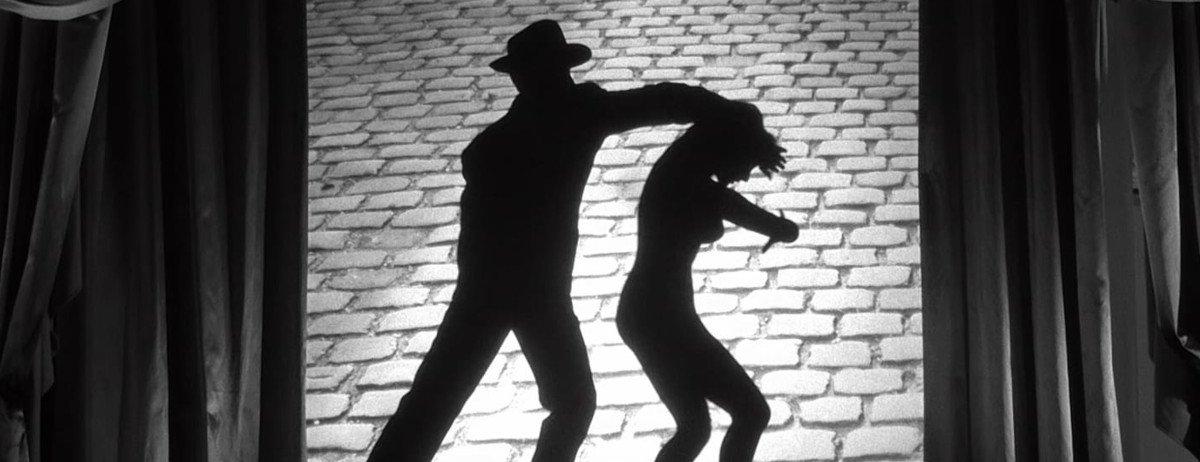 Ein Schattenspiel, das zeit, wie ein Mann mit Hut eine Frau von Hinten angreift