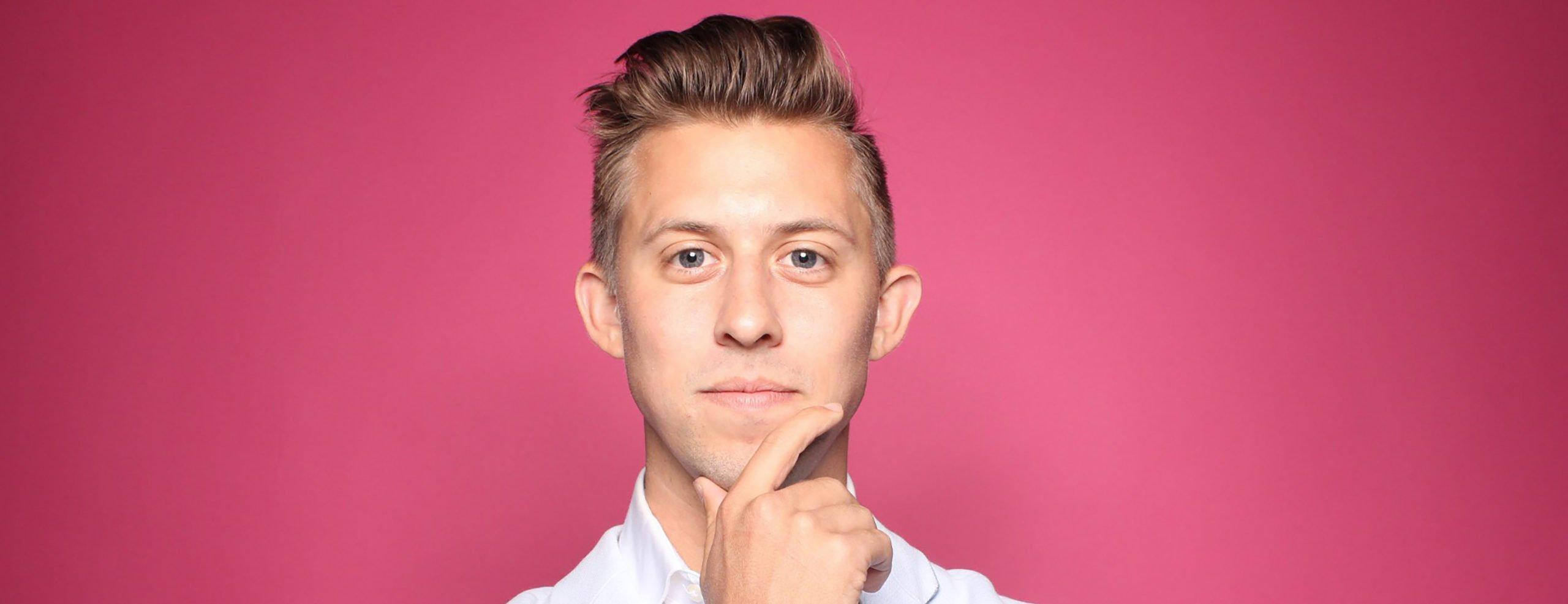 Ein junger, weißer Mann steht vor einem farbigen Hintergrund und greift sich fragend ins Gesicht