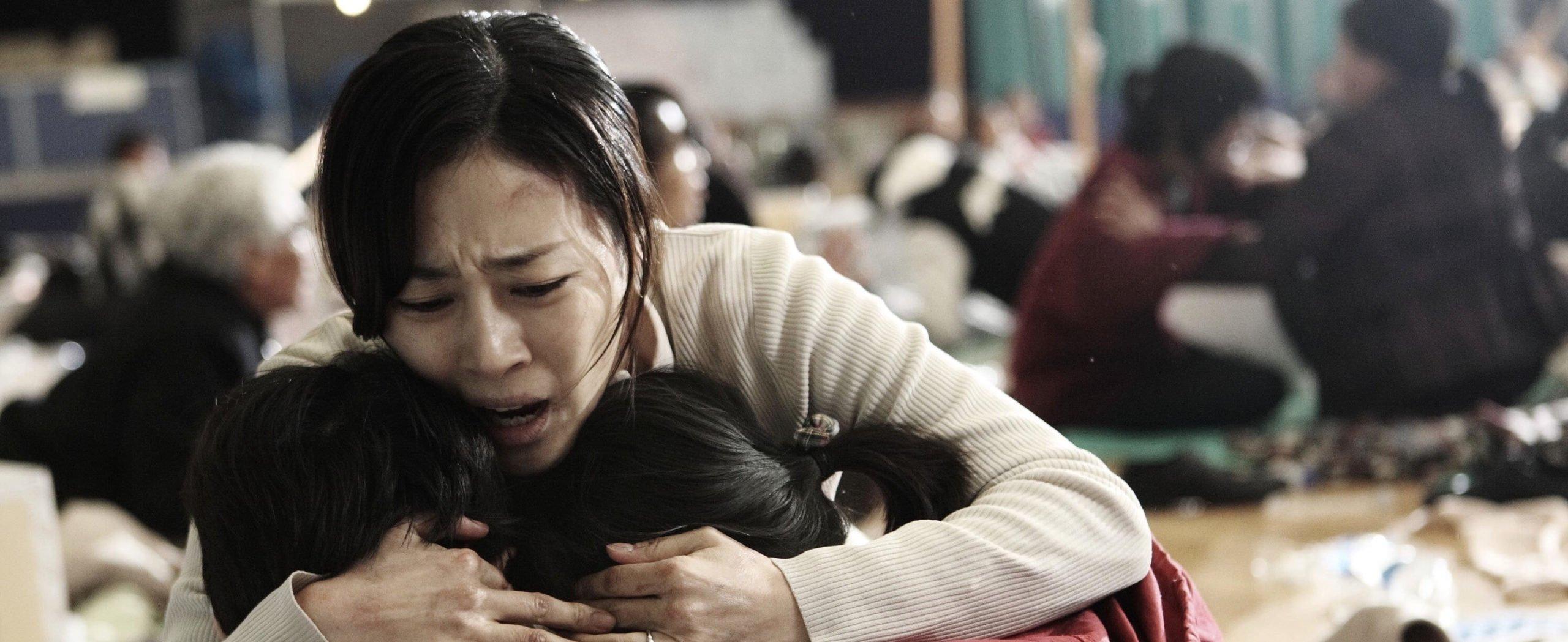 Eine Mutter kniet vor ihren Kindern und unarmt sie. Ihr Gesicht ist verzweifelt