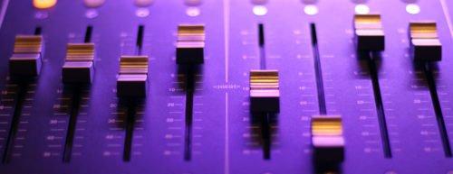 Ein Mischpult in violetter Farbe mit Reglern im Fokus