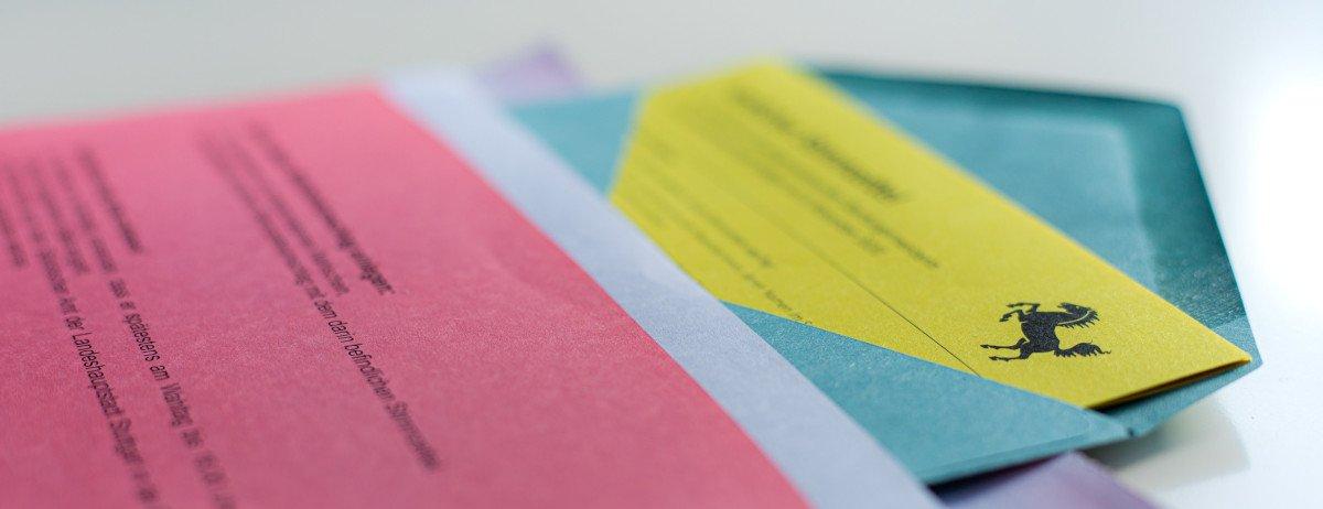 Ein pinkes Begleitschreiben liegt auf einem blauen Umschlag, in dem ein gelber Stimmzettel steckt