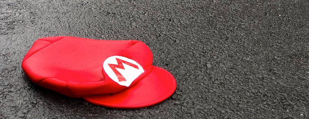 eine rote Mütze von Mario, die auf der grauen Straße liegt