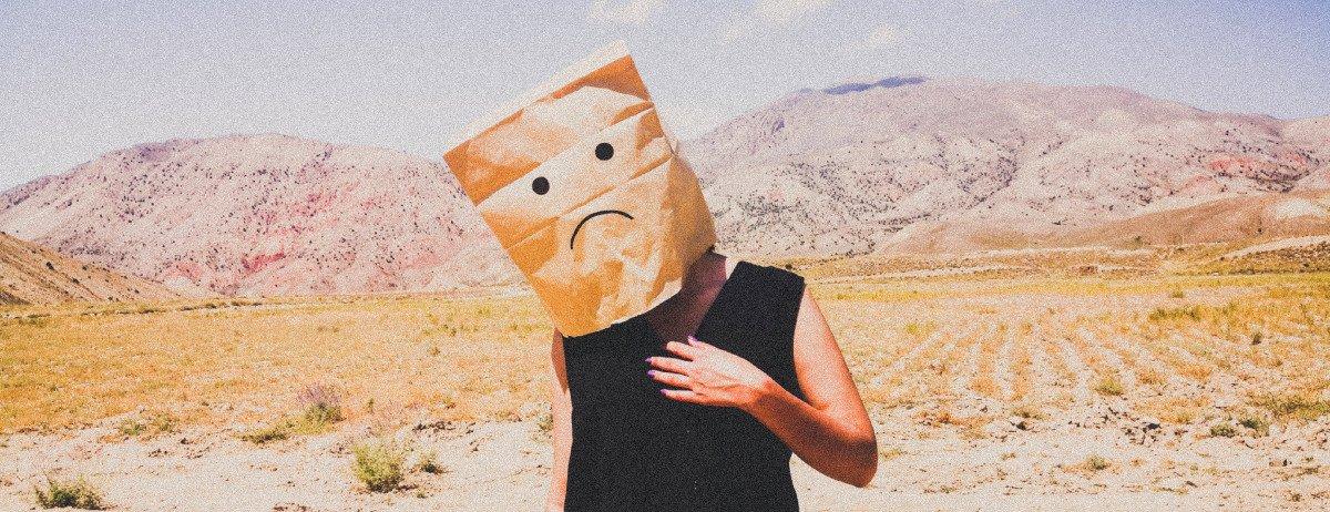 Mensch steht in der Wüste und hat eine Papiertüte über den Kopf, auf der ein trauriger Emoji gemalt ist