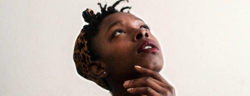 Eine Frau greift sich an das Kinn und schaut nachdenklich nach oben