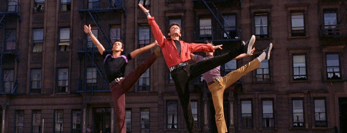 Drei Männer, die tanzen und dabei gerade ein Bein hoch in die Luft werfen