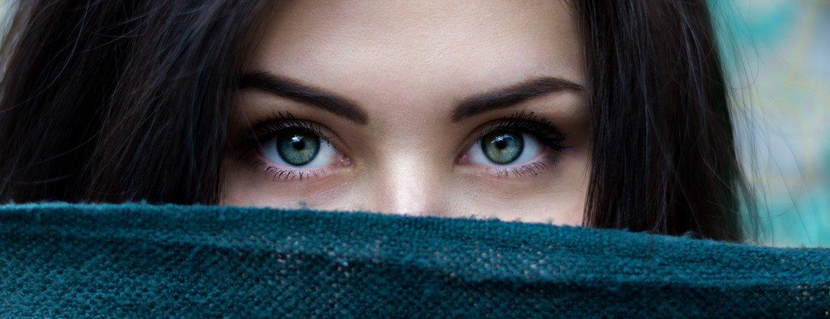 Eine junge Frau, die sich hinter einem Schal versteckt. Nur ihre Augenpartie ist sichbar