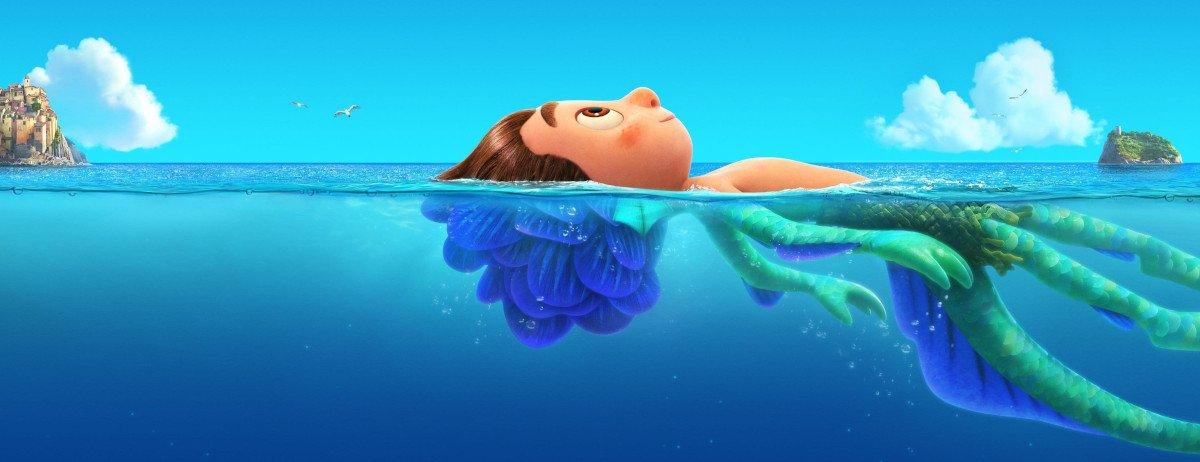 Luca liegt im Wasser. Über der Wasseroberfläche ist er ein Mensch, unter der Wasseroberfläche ein Seemonster mit Tentakeln