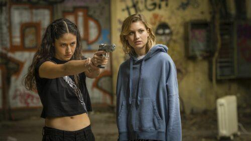 Eine junge Frau zielt mit der Pistole auf ein Ziel außerhalb des Bildes. Rechts von ihr eine weitere Frau, die auf das Ziel schaut.