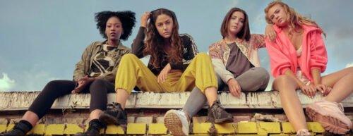 Die vier Protagonistinnen sitzen auf einer Mauer und schauen in die Kamera