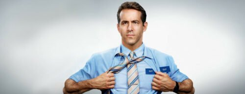 Ryan Renolds öffnet sein blaues Hemd, unter dem sich ein weiteres blaues Hemd befindet