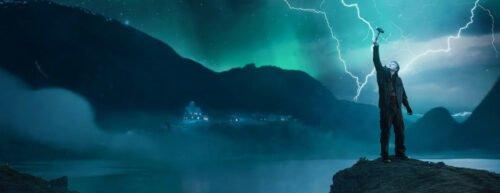 Der Hauptdarsteller hält auf einer Klippe Thors Hammer in die Luft, in den mehrere Blitze einschlagen
