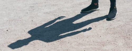 Ein Schatten einer Person, oben rechts sieht man deren Füße