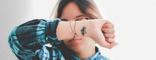 Eine junge Frau hält den Arm vor die Augen