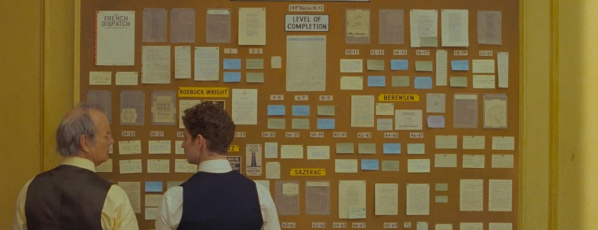 Zwei Verleger stehen vor einer Pinnwand voller Ideen für die Zeitung The French Dispatch